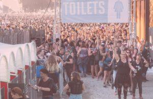 Groupe de femmes devant les cabines madamePee au Hellfest